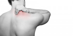 shoulder pain treatment. man holding this shoulder, gripping it as he is in pain